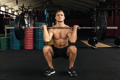 Young muscular man during his weightlifting workout in the gym