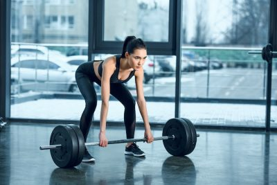 woman picking up a barbell