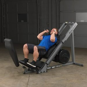 a man using the body solid leg press hack squat machine