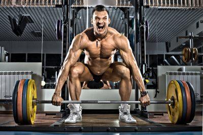 brawny bodybuilder prepairing to lift a barbell