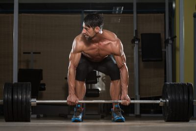 man gripping a heavy barbell