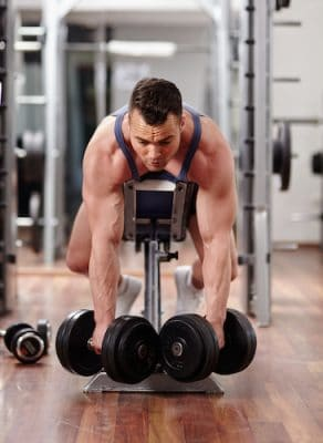 bodybuilder lifting heavy dumbbells