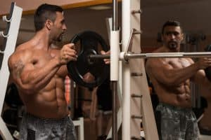 Body Builder Putting Weights On Bar In Gym