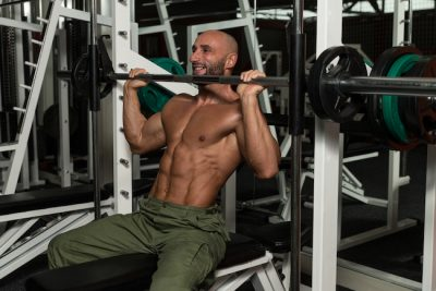 Man training his shoulders using the smith machine