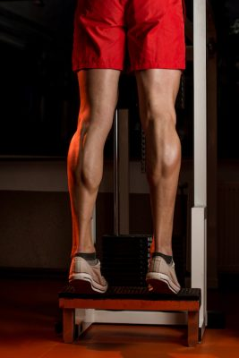 muscular man training his lower leg muscles in a gym