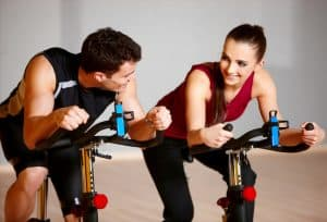 a man and a woman on exercise bikes at the gym