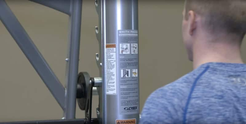a man looking at a safety placard on a resistance training machine