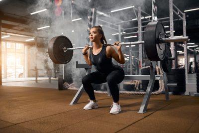 female doing barbell squats