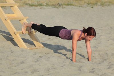 woman performing strength training on the beach
