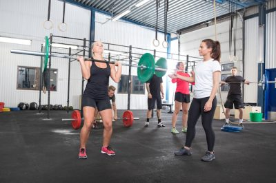 group of people lifting weights together in a gym