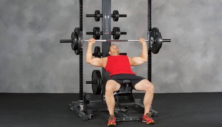 muscualr man in a vest doing incline presses