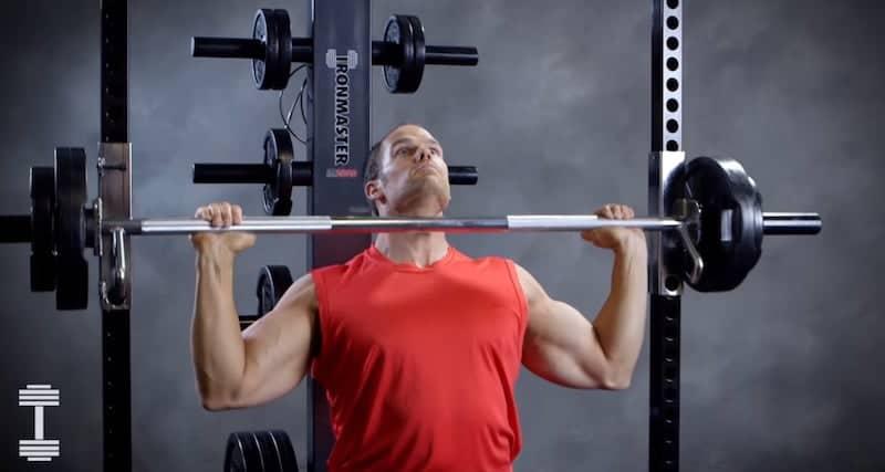 man pressing a heavy barbell