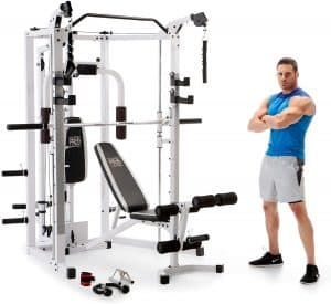 muscular man stood next to a gym machine with his arms folded