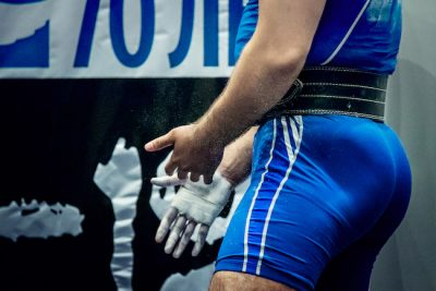 man putting chalk on his hands during a powerlifting meet