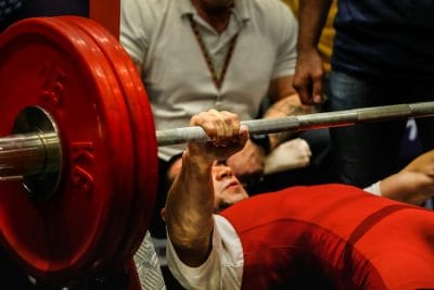 powerlifting gripping a barbell while laying on a bench