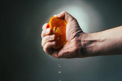 man squeezing an orange