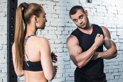 man flexing his arms for a woman in the gym