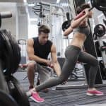 young man and woman working out in the gym