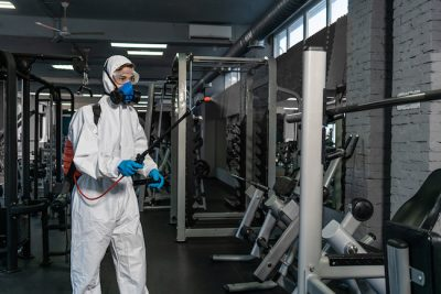 man cleaning gym equipment