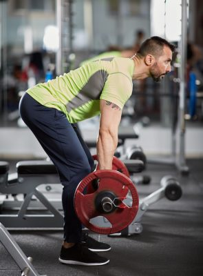 athletic man doing rows with a barbell