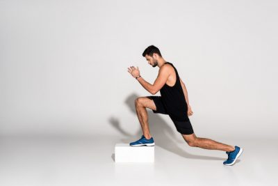 man doing lunges on a step up box