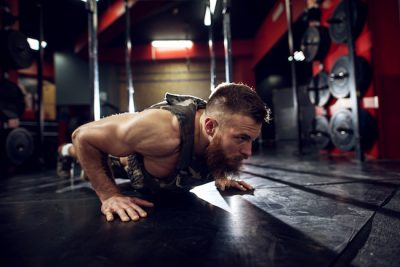 man doing push ups on the gym floor while wearing a weighted vest