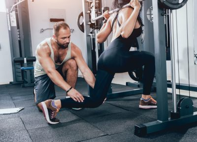 man instructing a woman while she works out