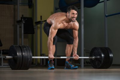 man gripping a loaded barbell