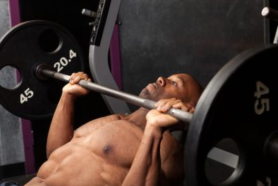 man performing the bench press in a gym