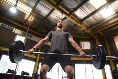 man doing olympic weightlifting in his gym