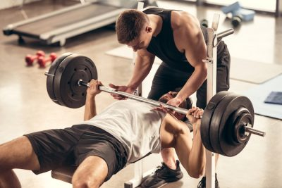man spotting his friend at the gymnasium