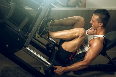 man using a leg press in the gym