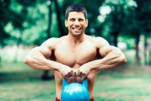 Muscular crossfit athlete exercising with kettle bell