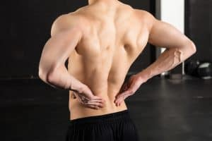 Close-up Of A Shirtless Man With His Back Pain Standing In The Gym
