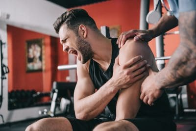 image of man wincing in pain while at the gym