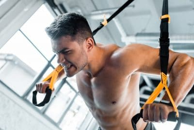 man working out on a suspention trainer
