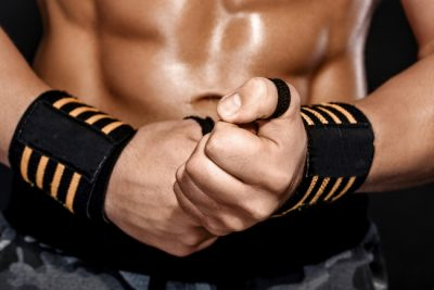 strong bodybuilder man wraps his wrist with sports wrap on black background