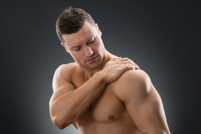muscular man suffering from shoulder pain against black background