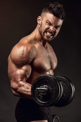 bodybuilder doing heavy dumbbell curls