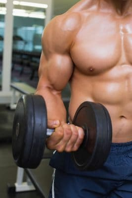 close up of a muscular man holding a dumbbell