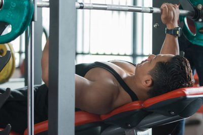 Muscular bodybuilder doing a bench press workout in a fitness centre