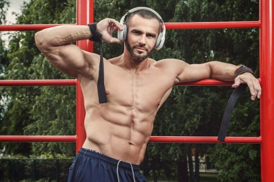Muscular man listening music during his street workout