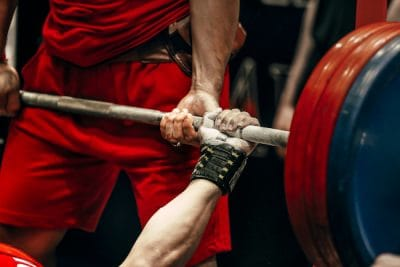 male athlete lifting a barbell at a powerlifting competition