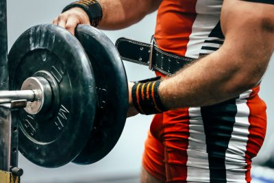 male powerlifting putting weights onto a barbell