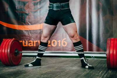 male athlete of powerlifting competition, preparing for attempt in deadlift