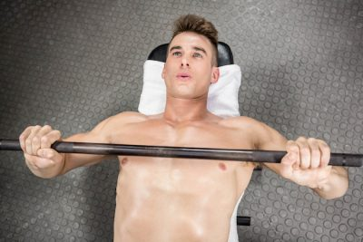 Shirtless man lifting heavy barbell on a bench