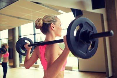 sporty woman exercising with a loaded barbell inside the gym