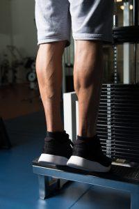 man training his calves on a gym machine