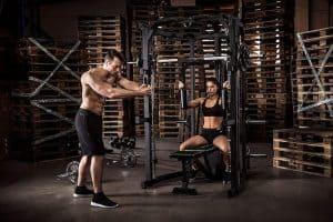an athletic man and woman performing resistance training exercises