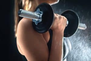 close up of a woman doing dumbbell curls